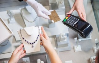 Young woman buying a golden necklace with blue gemstones and paying with a credit card
