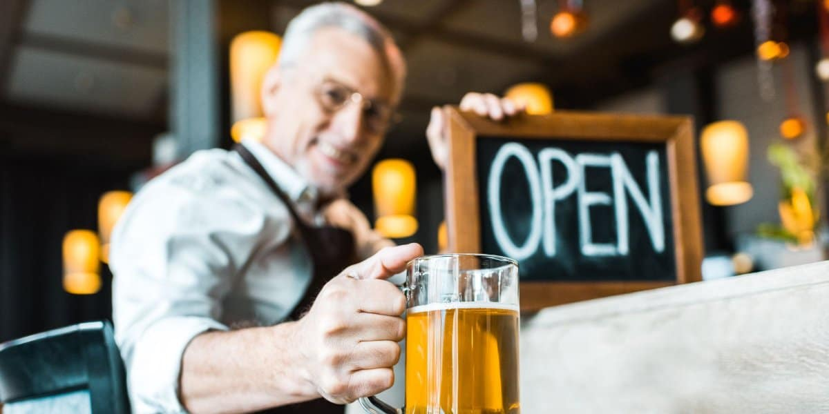 man with pub open sign